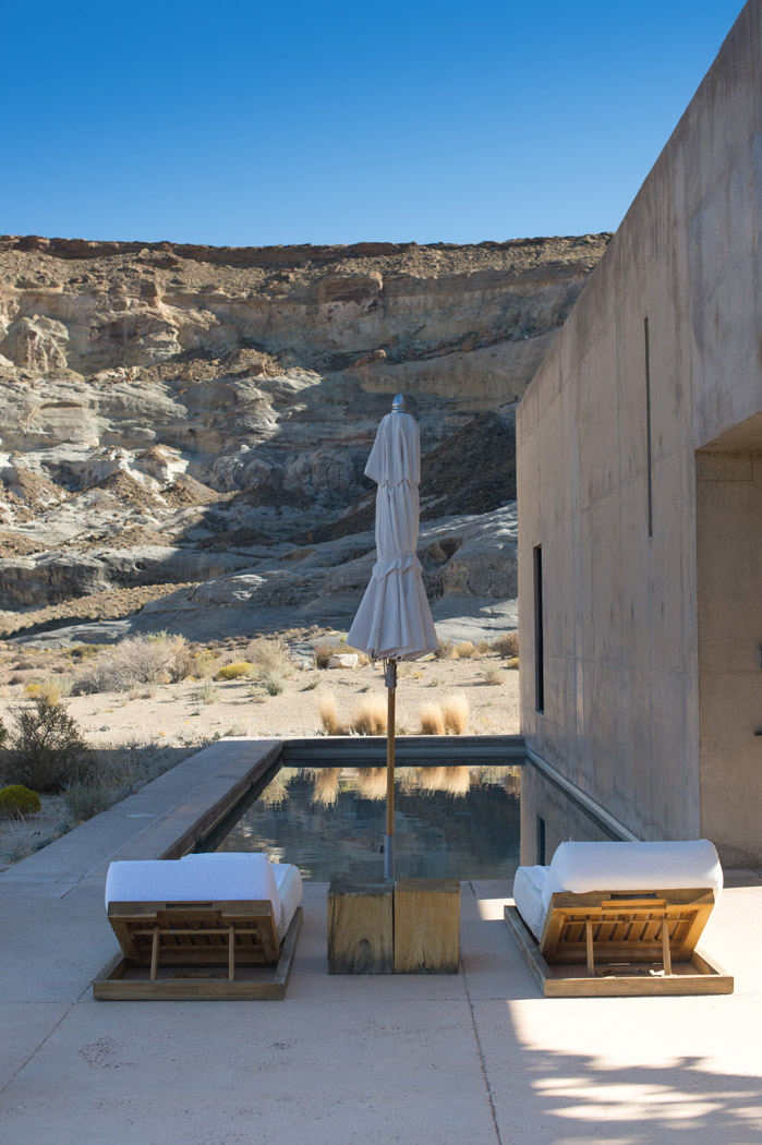 suite and two lounge chairs with view of the desert at amangiri
