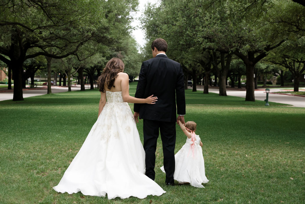bride and groom and flowergirl at Perkins Chapel lawn