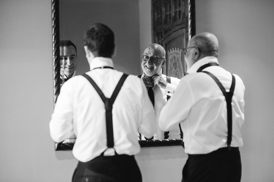 groom and father tying bow ties at a wedding in suspenders