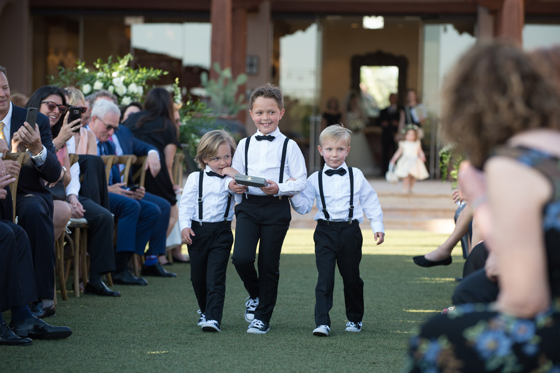 ring bearers coming down the aisle in suspenders and converse sneakers