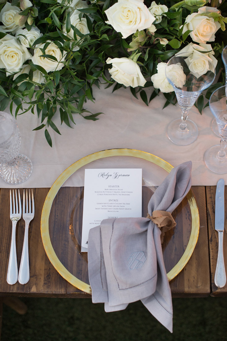 gold charges, gray monogram napkins, white roses and greenery centerpieces. Design by Imoni Events