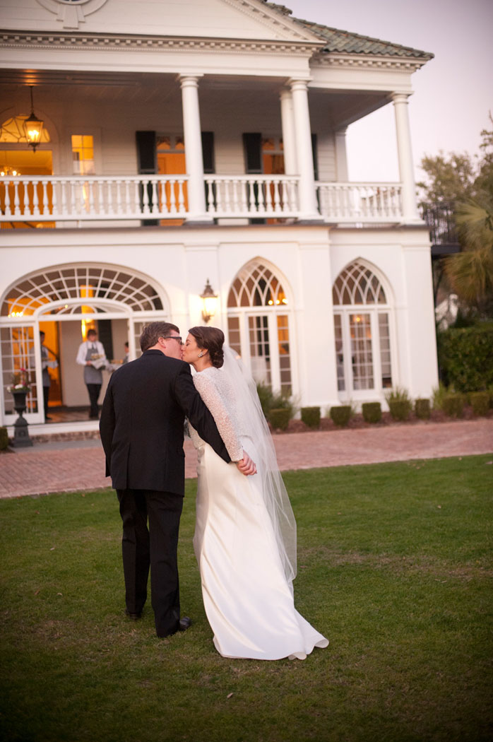 bride and groom kiss at sunset in front of Lowndes Grove