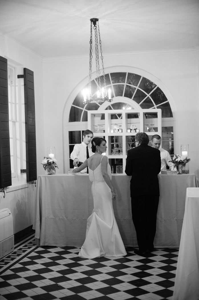 bride and groom at bar with black and white tile at Lowndes Grove