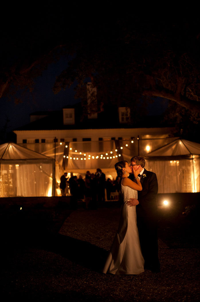 bride and groom kiss after dark in front of their tented wedding at Lowndes Grove