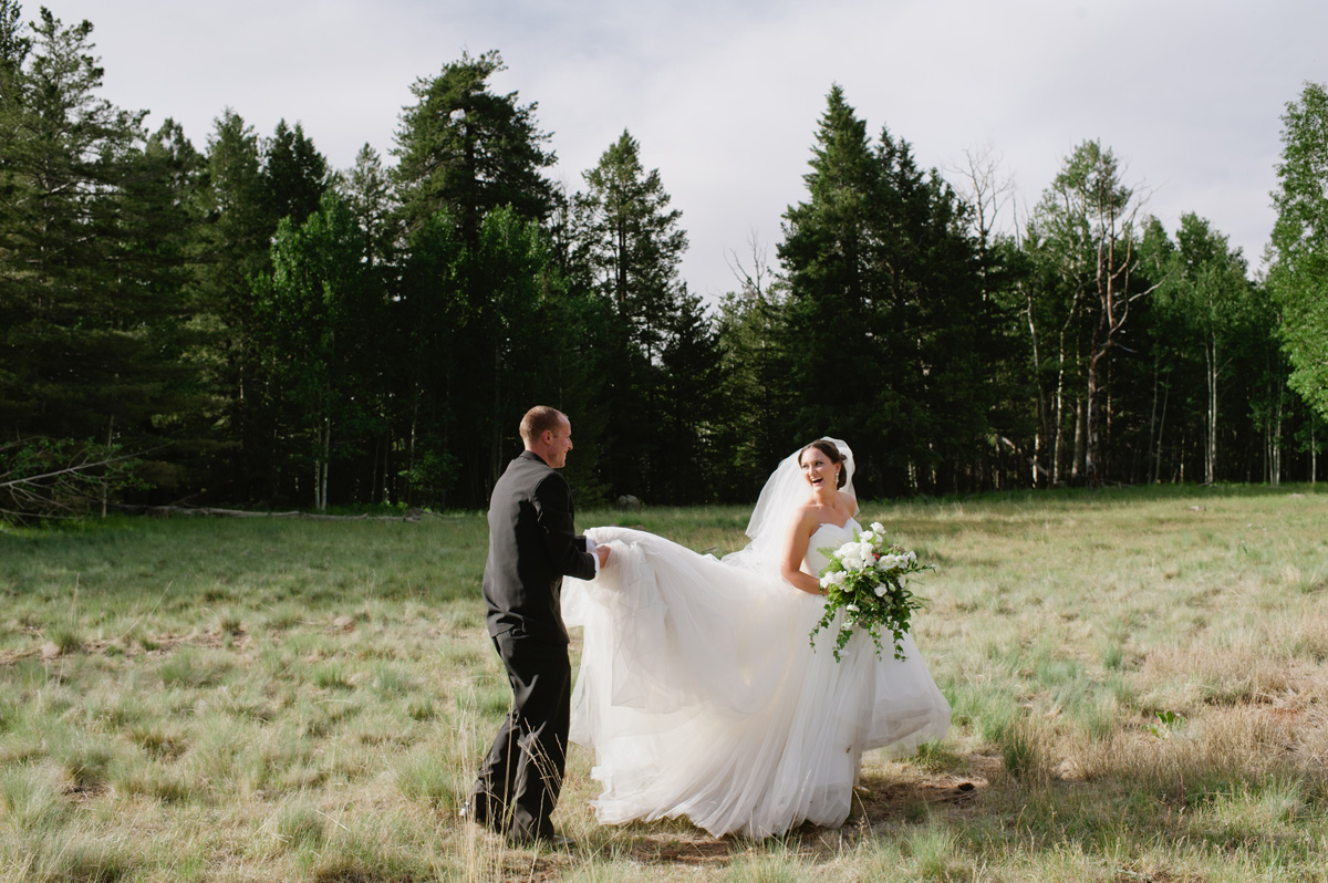Bride and groom laughing in a prairie in Flagstaff