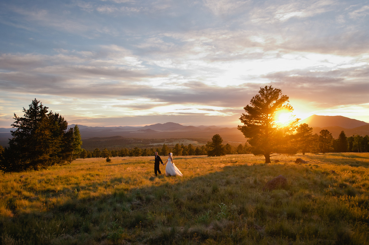 bride and groom walking during sunset in Hart Prairie at Arizona Snowbowl