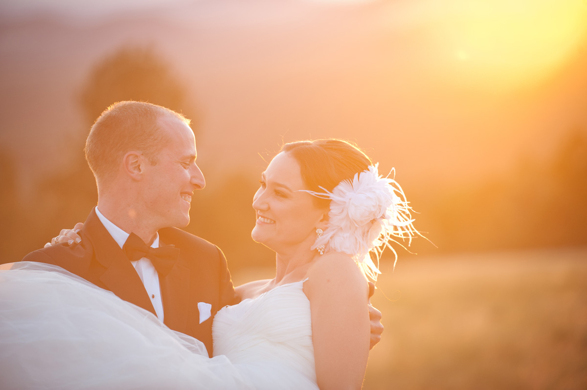 groom picking up bride during sunset in Hart Prairie at Arizona Snowbowl