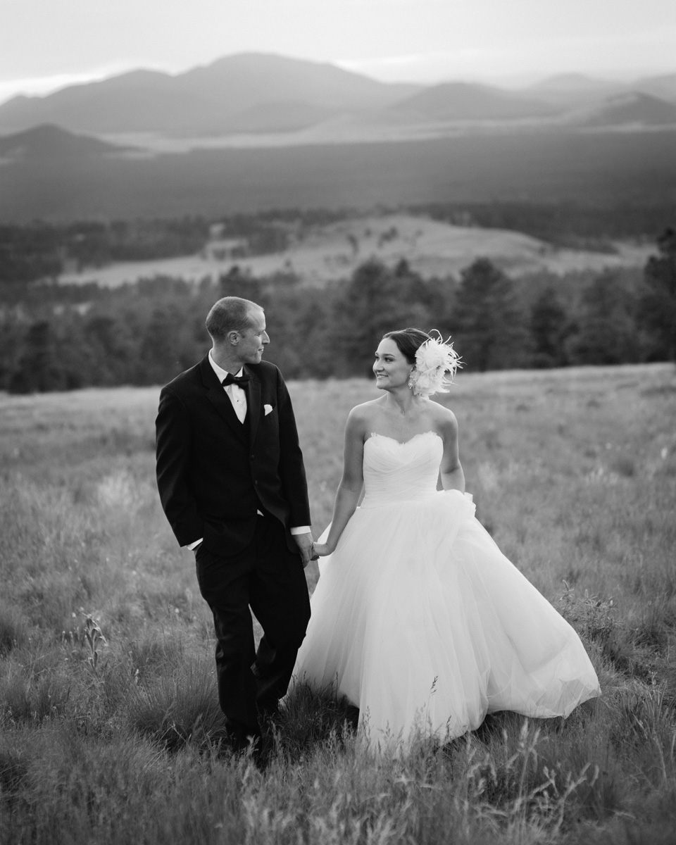 bride and groom walking hand in hand after sunset in Hart Prairie at Arizona Snowbowl