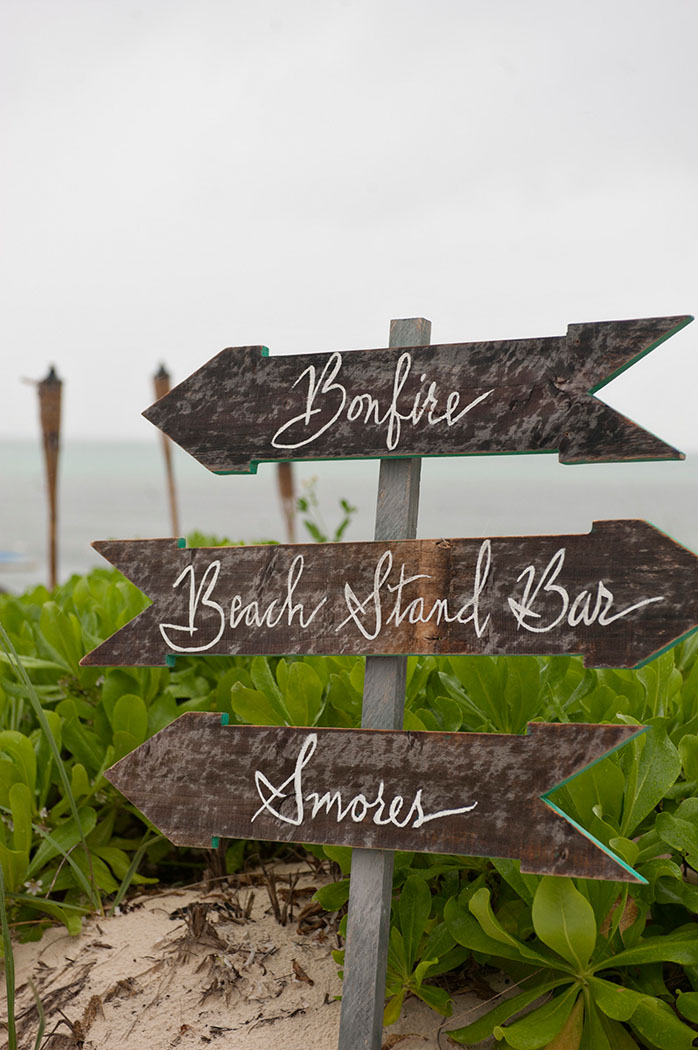 Handwritten arrow signs for a beach welcome party