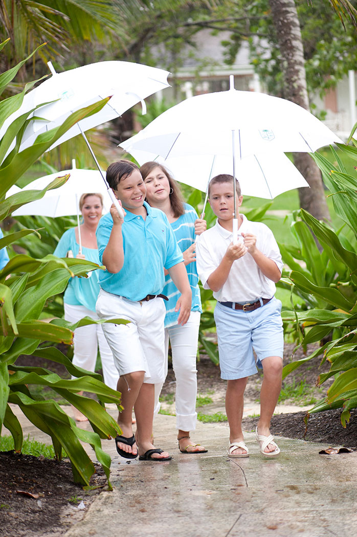 cousins in blue and white walking with umbrellas to a lyford cay beach welcome party