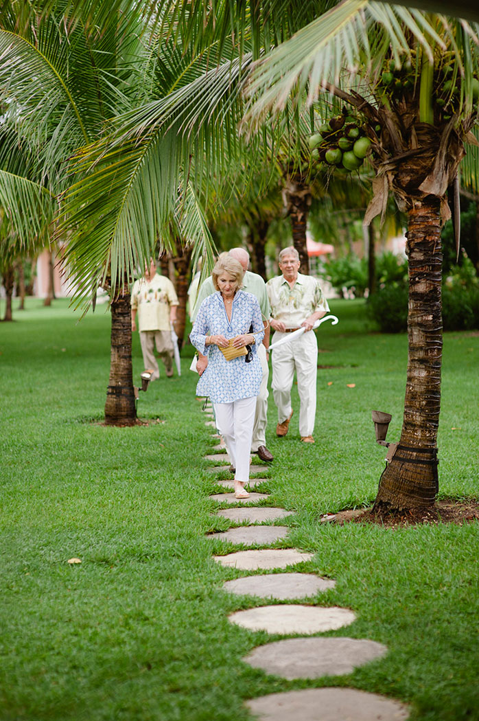 guests walking under the palm trees on a stone path to a lyford cay party