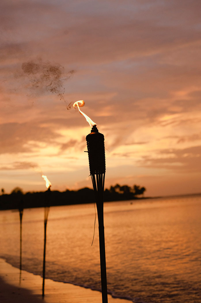 tiki torch burns yellow at sunset at a lyford cay beach