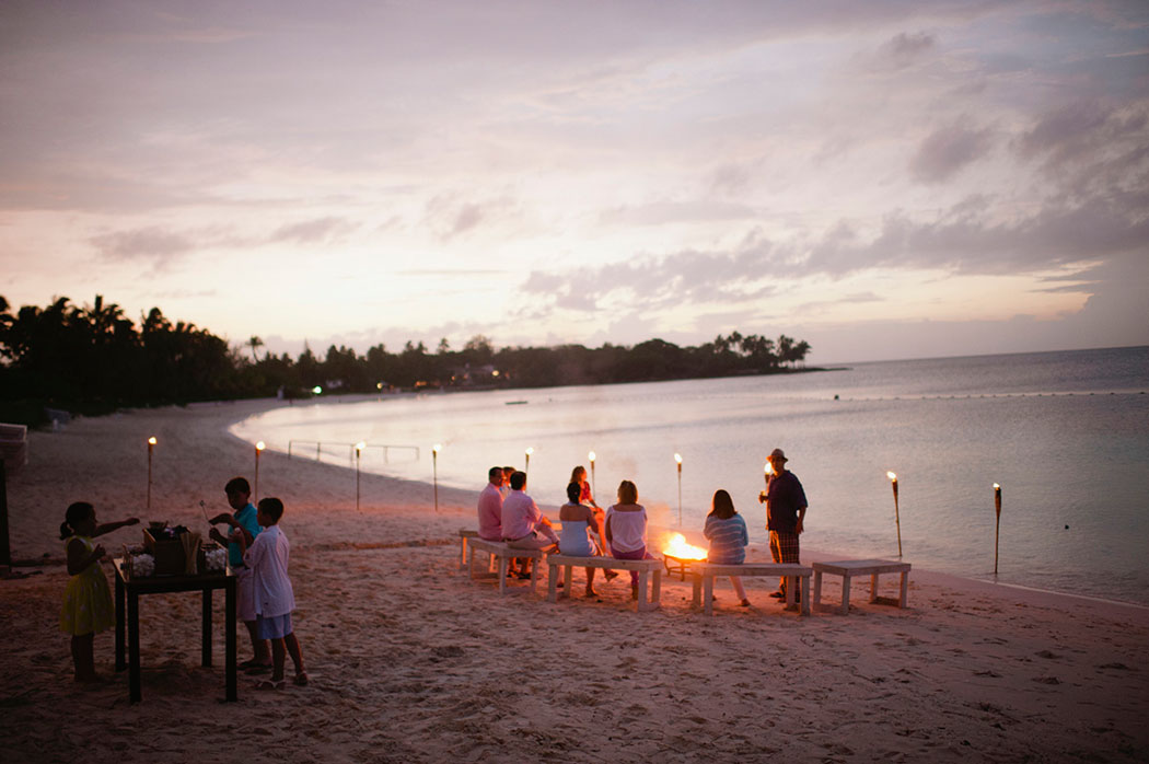 kids make smores during the sunset at a lyford cay beach welcome party