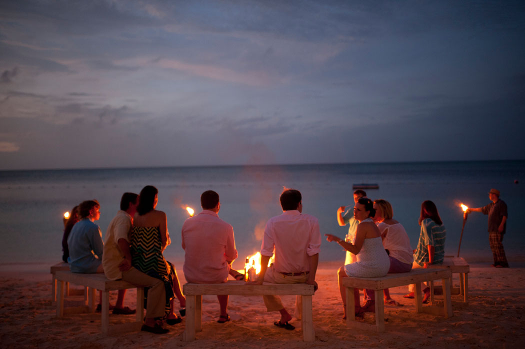 guests chat after sunset at a lyford cay welcome party bonfire