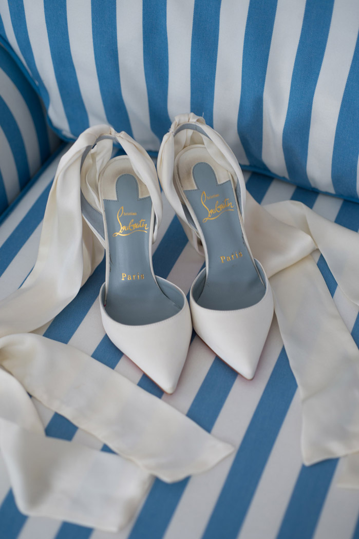 Christian Louboutin Douce du Desert ankle tie pumps on a blue and white sofa