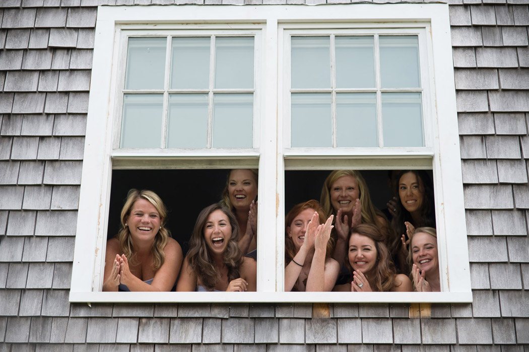 Bridesmaids looking out a shingled house during the first look at Mackenzie's Nantucket Wedding