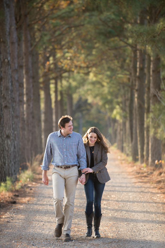 couple walking through a driveway of pine trees