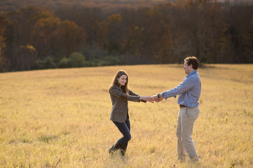 couple holding hands and standing in a field