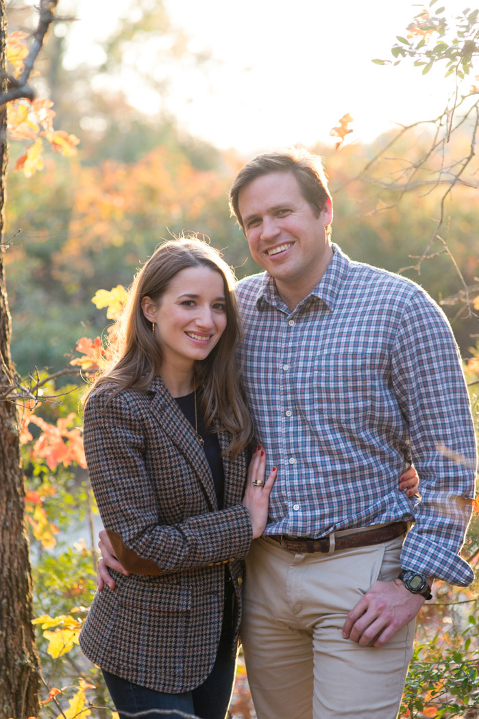 engaged couple standing in yellow fall light