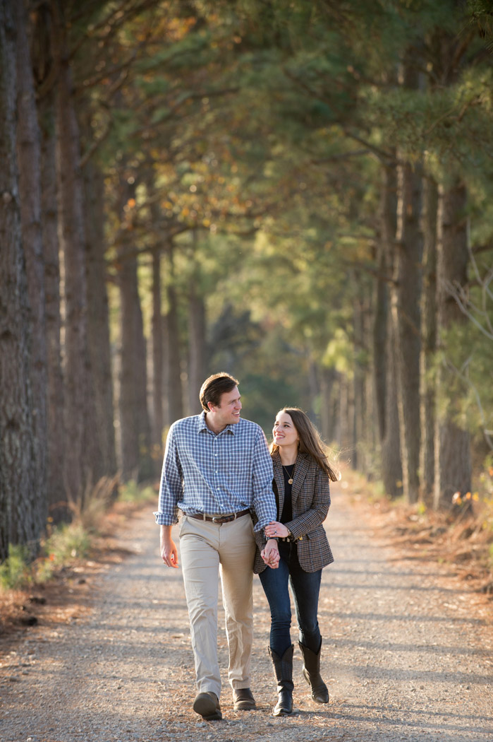 couple lovingly looking at each other walking down a driveway lined with pine trees
